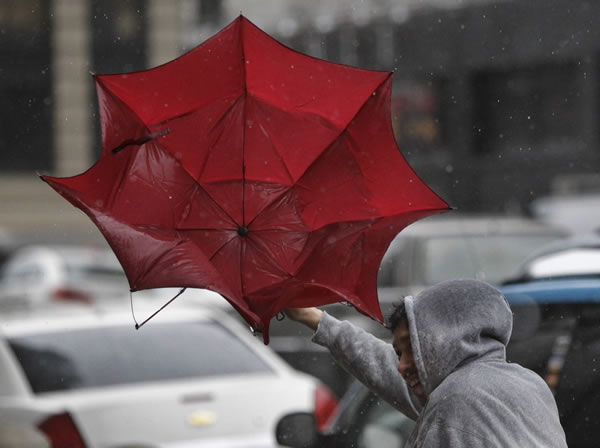 A man's umbrella goes inside out during a windy rain storm, Thursday, March 24, 2011, in San Francisco. (AP Photo/Paul Sakuma)