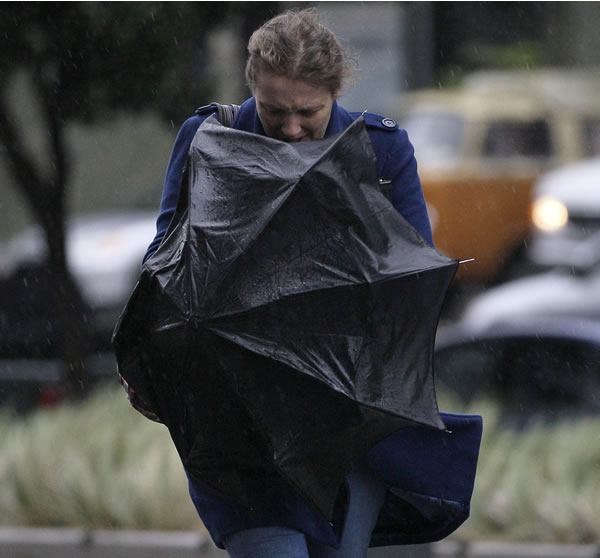 A woman struggles with an umbrella while walking toward the federal courthouse building in San Francisco, Thursday, March 24, 2011. (AP Photo/Jeff Chiu)