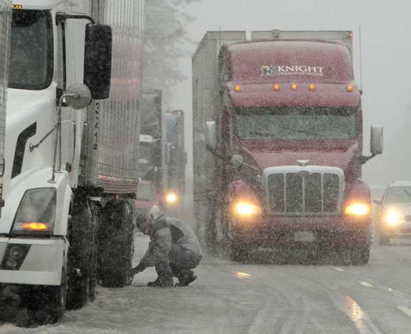 A trucker chains-up on eastbound Interstate 80 near Alta, Calif., Thursday March 24, 2011. Storms swept through the Sierra Nevada forcing drivers to chain up to cross over Donner Summit. (AP Photo/Rich Pedroncelli)