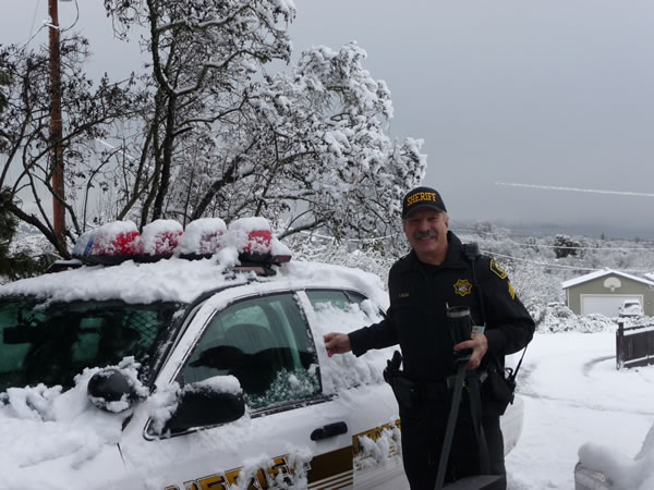 Sgt. Gary Basor of the Lake County Sheriff's office with snow on his patrol car in Lakeport, Calif.