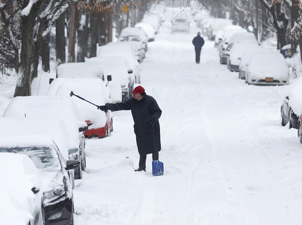 A man clears snow from a vehicle on Friday, Jan. 3, 2014, in Albany, N.Y.