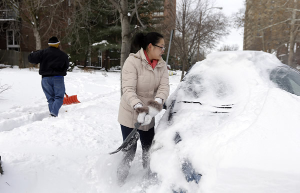Cecy Wang, right, clears snow off her car as Samuel Scott, left, shovels a sidewalk Tuesday, Jan. 7, 2014, in St. Louis. As Missourians muddled through another frigid day Tuesday, the worst cold snap in nearly two decades was about to come to an end but many roads remained partly snow-covered two days after a winter storm dumped several inches of snow. (AP Photo/Jeff Roberson)