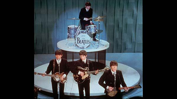 The Beatles perform on the Ed Sullivan Show during the bands first American appearance in New York City, Feb. 9, 1964. From left in front row are, Paul McCartney, George Harrison and John Lennon. Drummer Ringo Starr is at rear. (AP Photo)