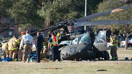 Officials examine a helicopter after it crashed on the campus of Texas A&M University on Monday afternoon, Jan. 12, 2009 in College Station, Texas. (AP Photo/Wade Barker)