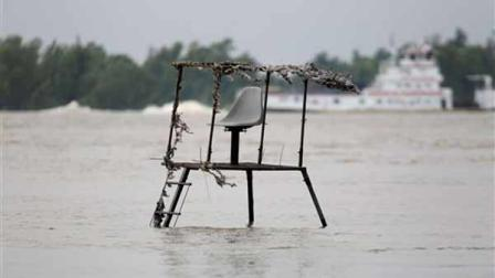 A deer blind sits mostly submerged in floodwaters as a tugboat pushes barges along the Mississippi River in the background in St. Francisville, La., Friday, May 20, 2011. Residents were leaving in the face of a mandatory evacuation order set to kick in on Saturday as Mississippi River water flowing through the Morganza spillway is expected to reach communities in the Atchafalaya Basin. (AP Photo/Gerald Herbert)
