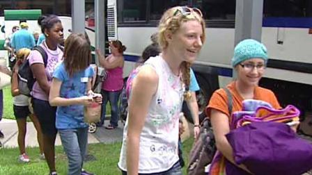 Children line up and load buses bound for Camp Periwinkle