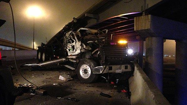 Garbage truck strikes bridge overpass