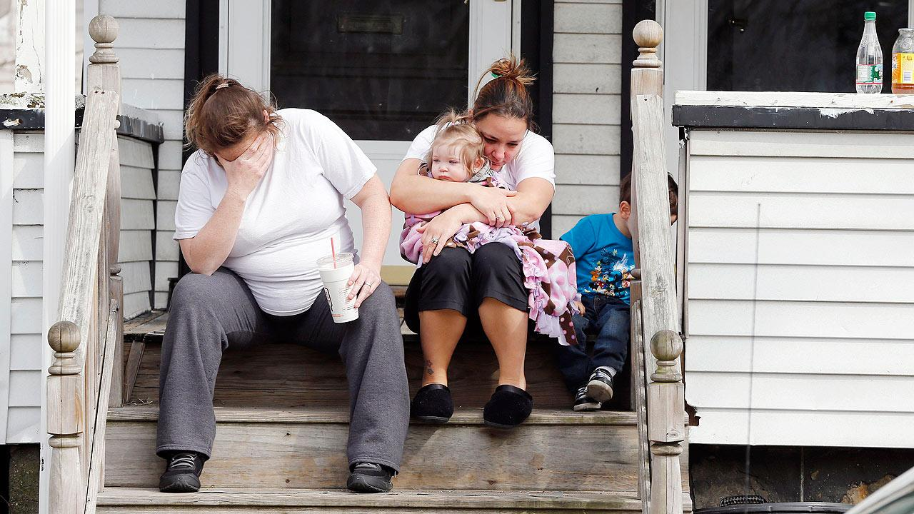 Neighbors sit outside the house of Krystle Campbells parents in Medford, Mass.,Tuesday, April 16, 2013. Campbell was killed in Mondays explosions at the finish line of the Boston Marathon. (AP Photo/Michael Dwyer)