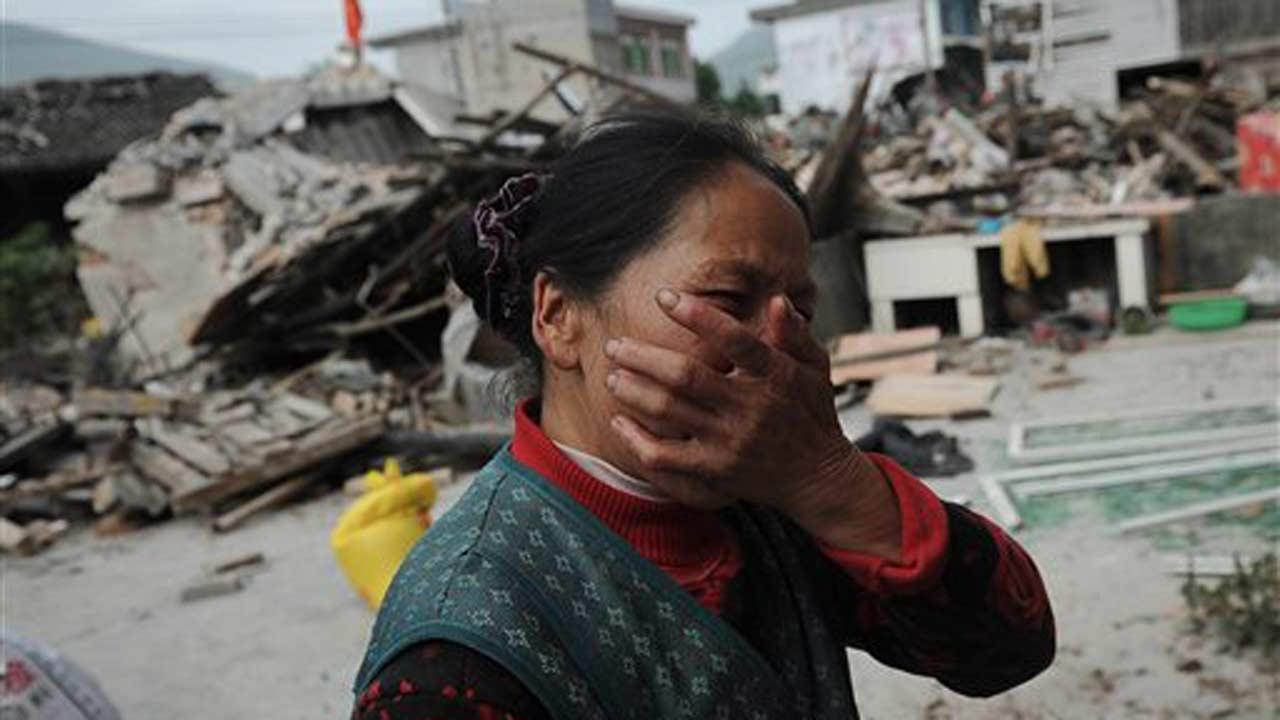 A village woman reacts after her house was damaged by an earthquake in Lushan county, Yaan, southwest Chinas Sichuan province on Saturday, April 20, 2013. The powerful earthquake struck the steep hills of Chinas southwestern Sichuan province Saturday, nearly five years after a devastating quake wreaked widespread damage across the region. (AP Photo)