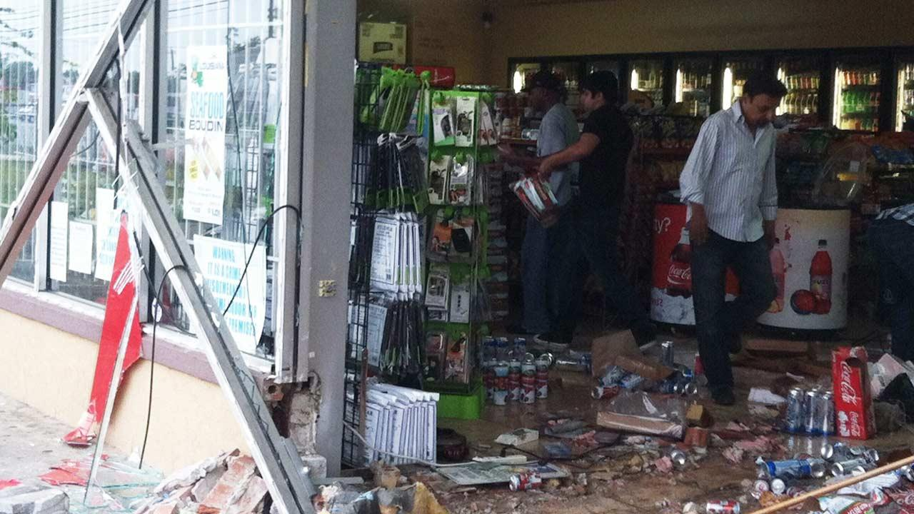 Employees work to pick up the debris after a smash-and-grab burglary at a convenience store in northeast Harris County <span class=meta>(Simon Gutierrez)</span>