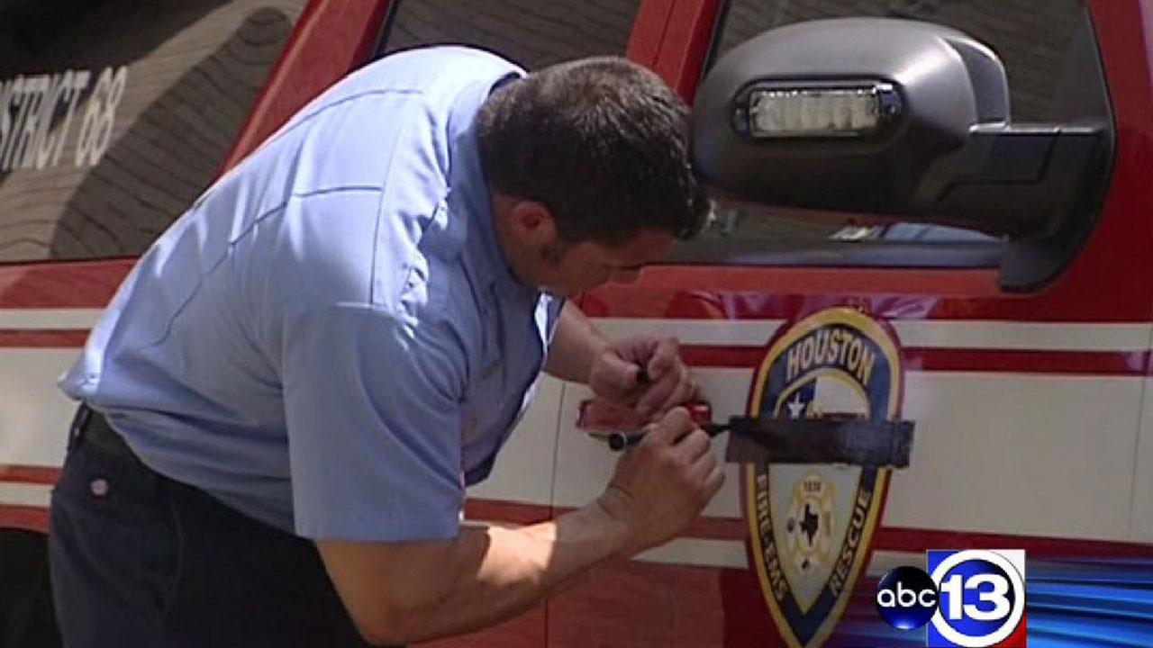 A firefighter places a black bar over the HFD shield, a sign of respect for fallen comrades