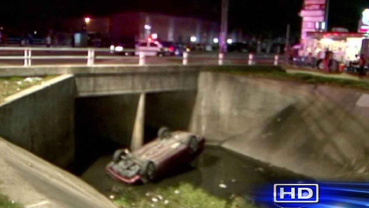 Officials say the driver of this car died after flipping over the bridge and plunging 30 feet into the ditch
