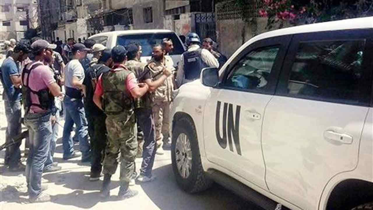 Syrian rebels escorted the UN investigation team, in Damascus countryside of Zamalka, Syria, Wednesday, Aug. 28, 2013