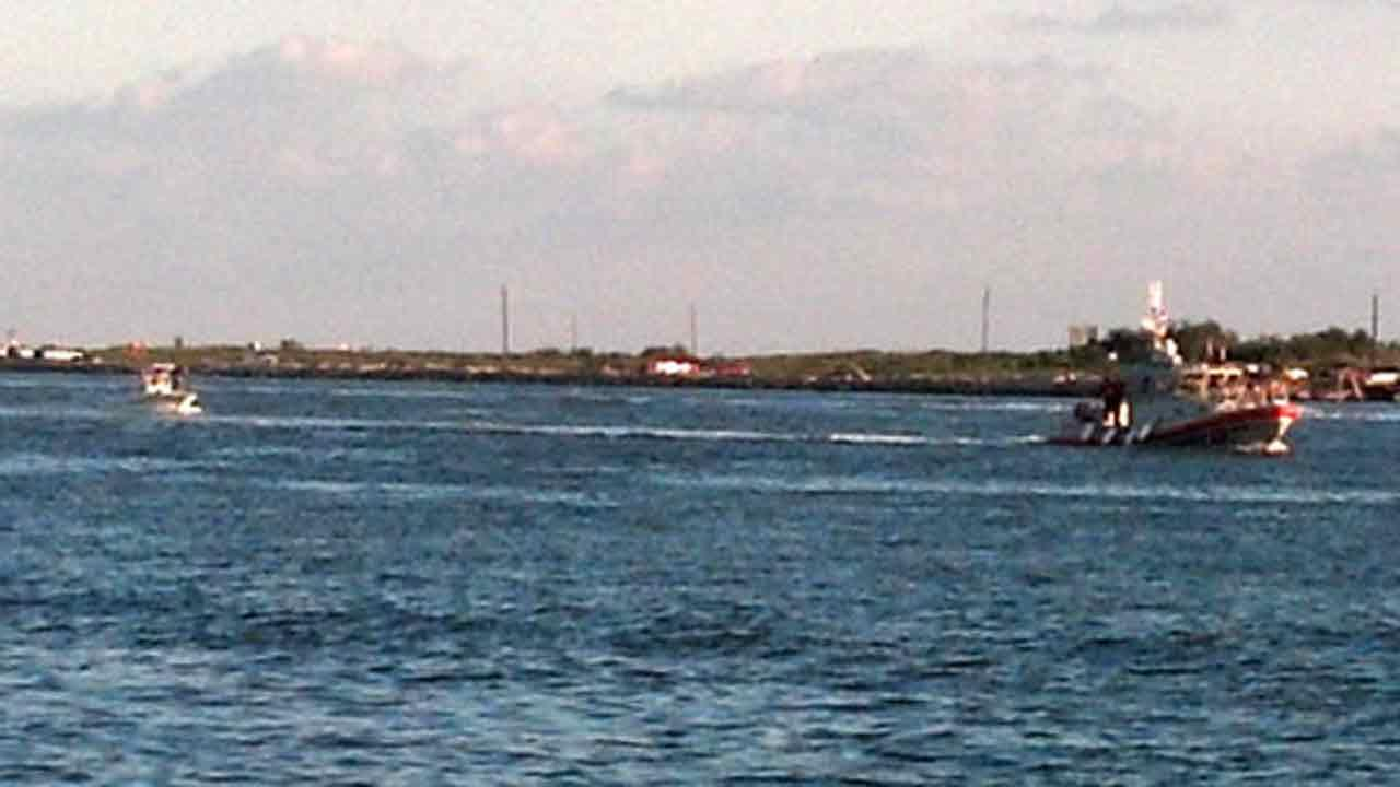 A boat crew aboard a 45-foot Response Boat - Medium, tows a disabled boat and two people to safety