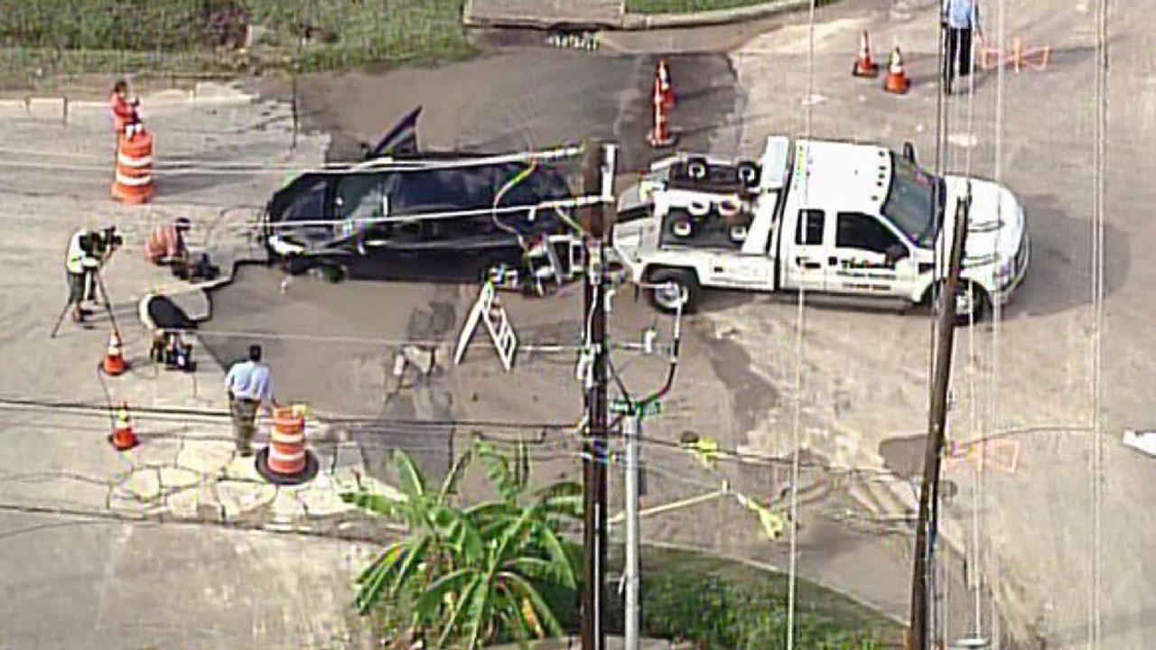 A large sinkhole opened up Monday in southwest Houston, trapping a woman in a car