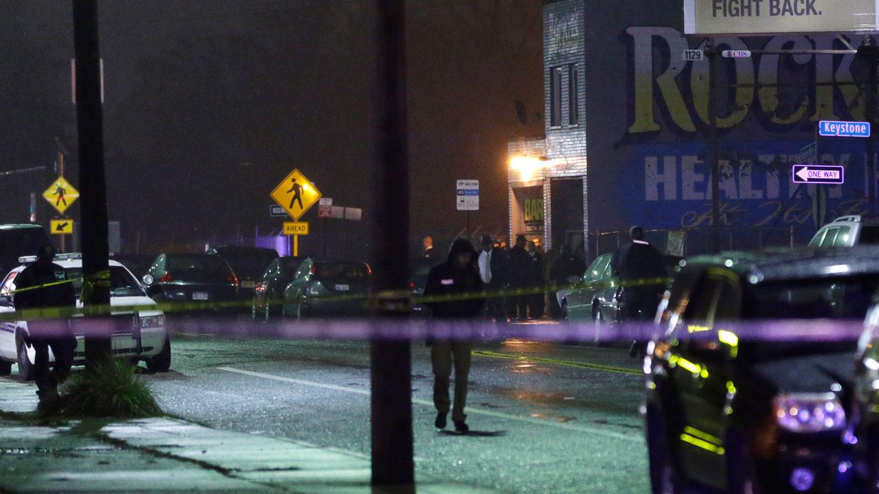 Police stand outside the scene of a multiple shooting near Rockies Barber Shop in Detroit, Wednesday, Nov. 6, 2013. Detroit police say gunfire broke out at the barbershop known for gambling activity. Police Chief James Craig told reporters that police were looking for two vehicles that the suspects may have been using, a 2004 white Chevrolet Impala that may have a broken window and bullet holes in the back, and a 2004 black Impala. (AP Photo/Carlos Osorio)