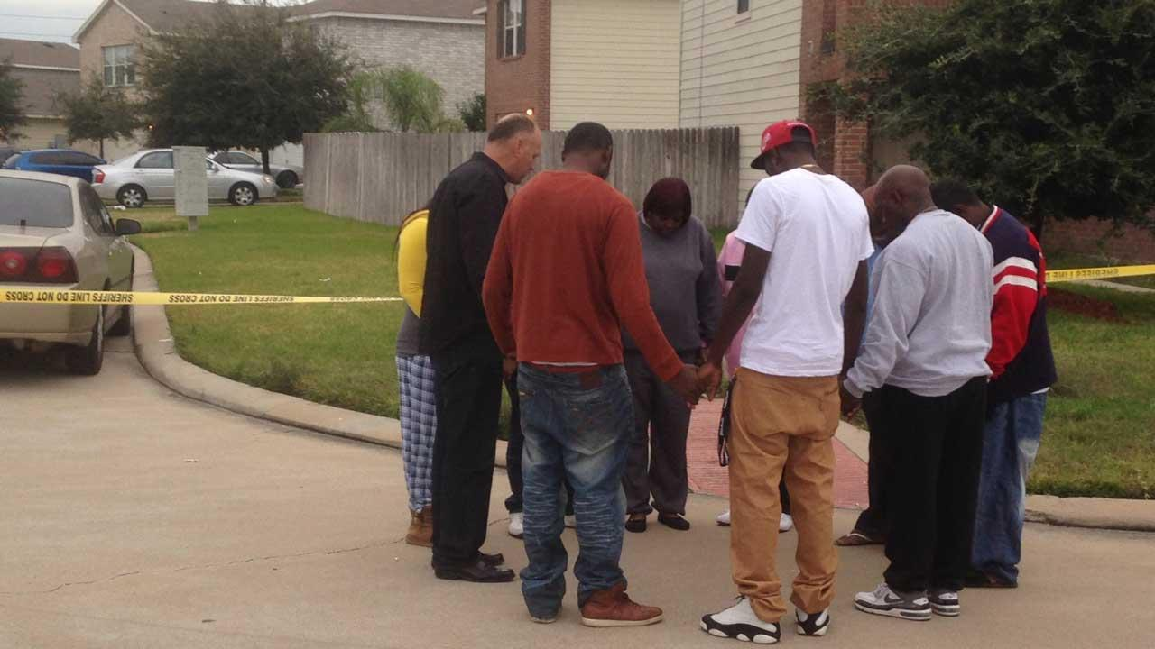 People hold hands and pray outside a crime scene in Cypress where two people died and 19 others were injured in a shooting at a party <span class=meta>(Simon Gutierrez)</span>