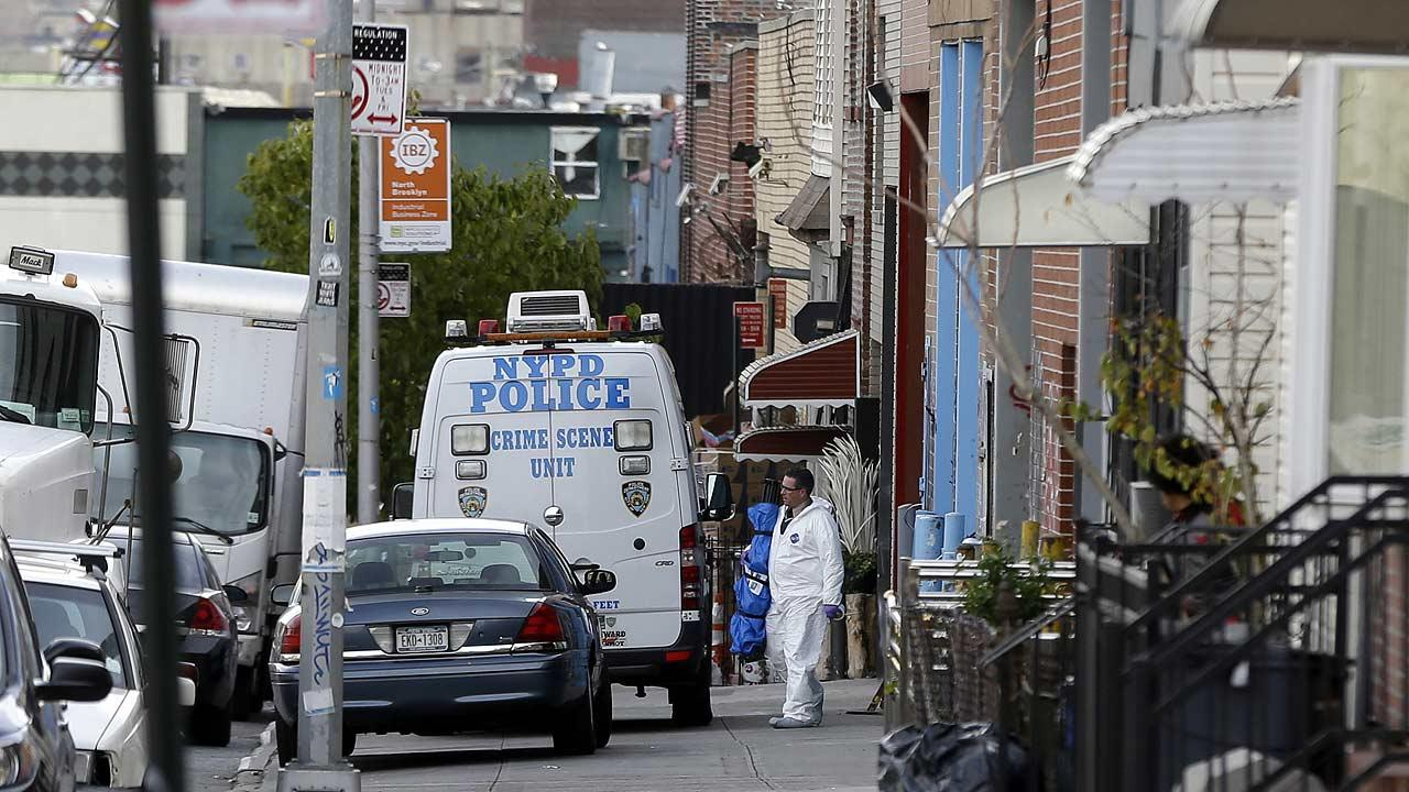 Crime scene personnel work at a crime scene in the Brooklyn section of New York