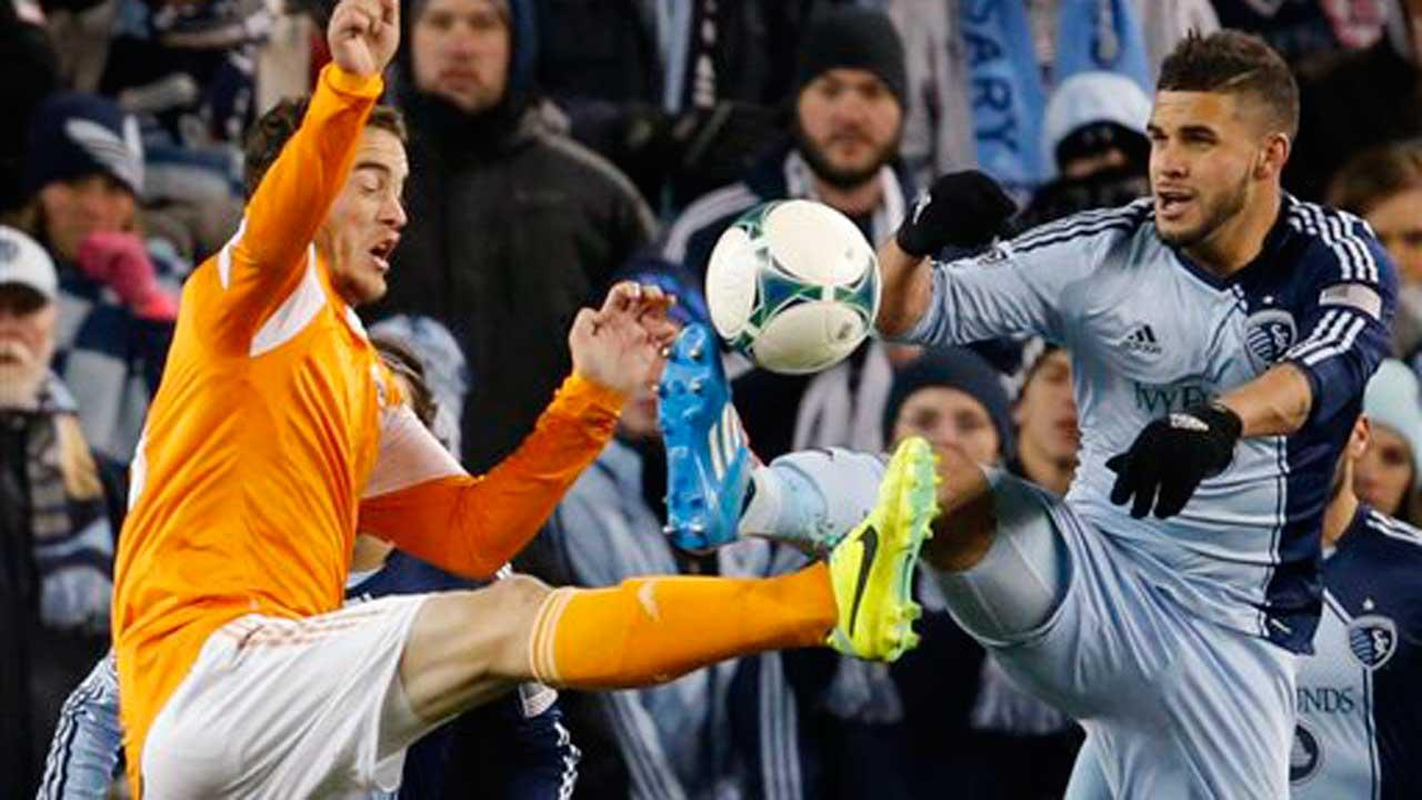 Houston defender Eric Brunner, left, and Sporting KC forward Dom Dwyer, right, battle for the ball during the second half of an MLS playoff soccer match in Kansas City, Kan., Saturday, Nov. 23, 2013. Sporting KC defeated Houston Dynamo 2-1
