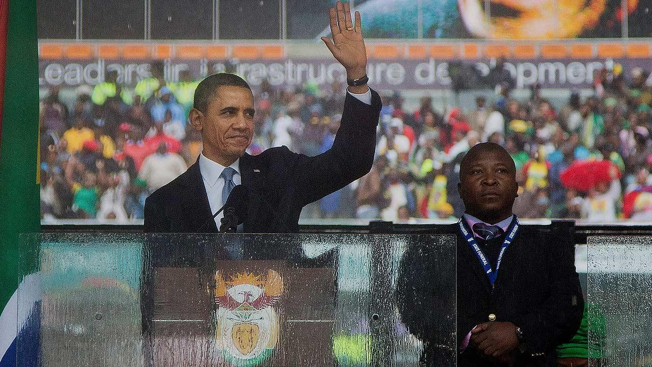 President Obama and man on stage at Nelson Mandela memorial