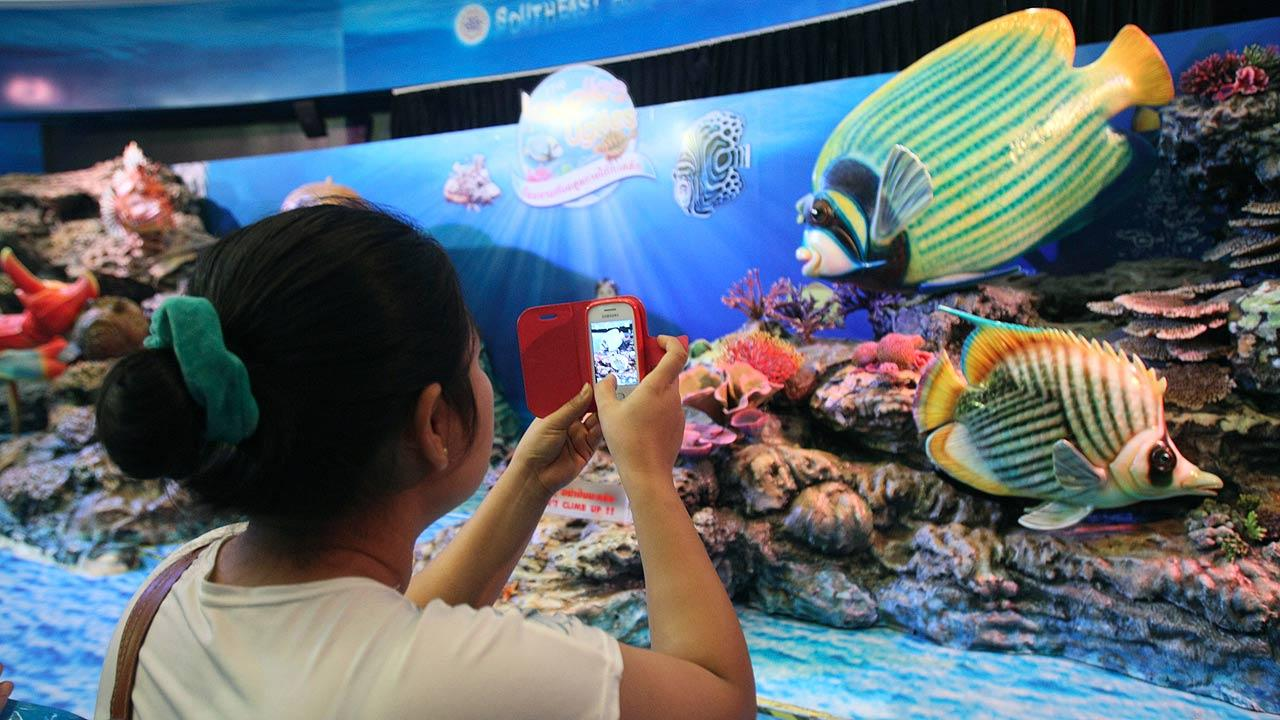 A visitor uses her mobile phone to take a picture of an aquatic animal display at Siam Ocean World, located in Siam Paragon shopping mall in Bangkok