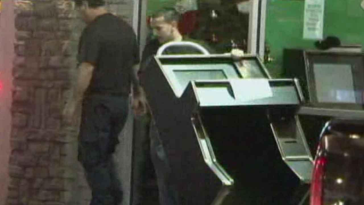 Authorities carry seized machines out of a game room in northeast Houston