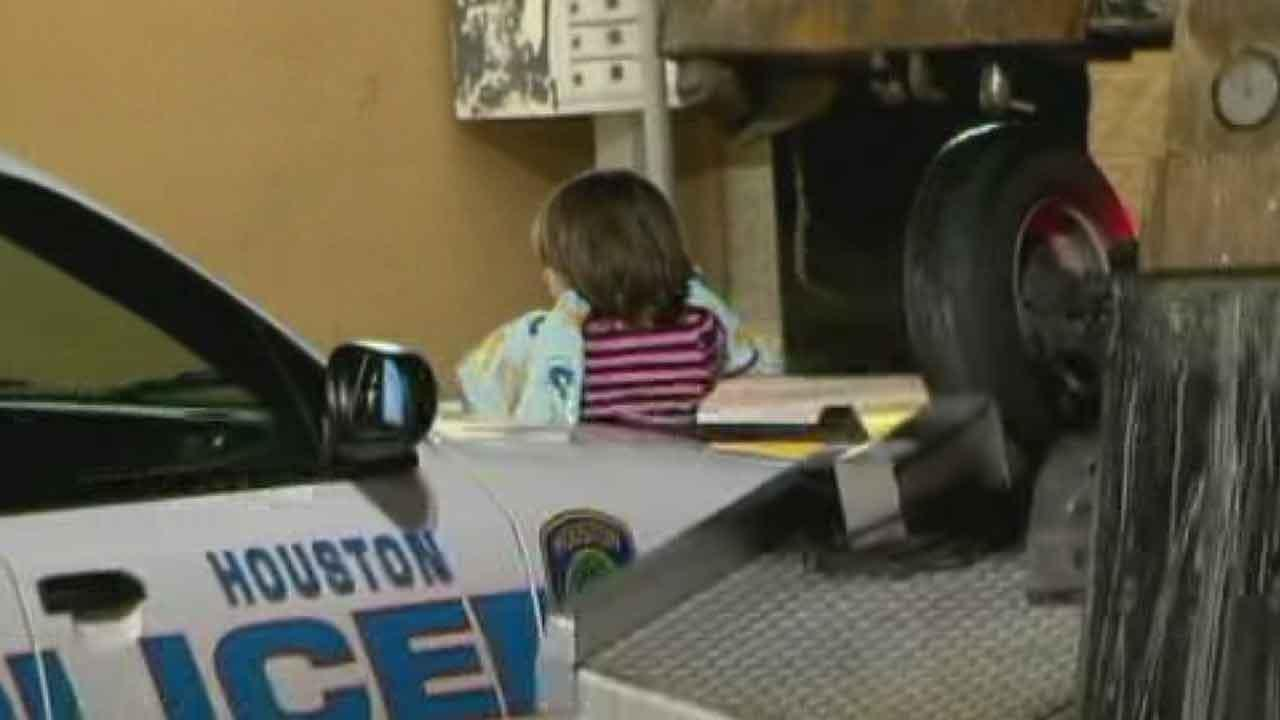 A five-year-old girl waits in front of a police car while officers question her mother about allegedly shoplifting