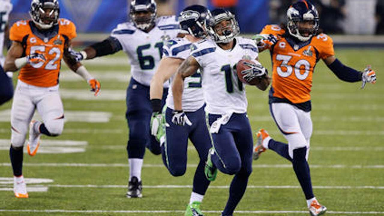 Seattle Seahawks Percy Harvin (11) runs from Denver Broncos David Bruton (30) while returning a kickoff 87-yards for a touchdown during the second half of the NFL Super Bowl XLVIII football game Sunday, Feb. 2, 2014, in East Rutherford, N.J. (AP Photo/Ted S. Warren)