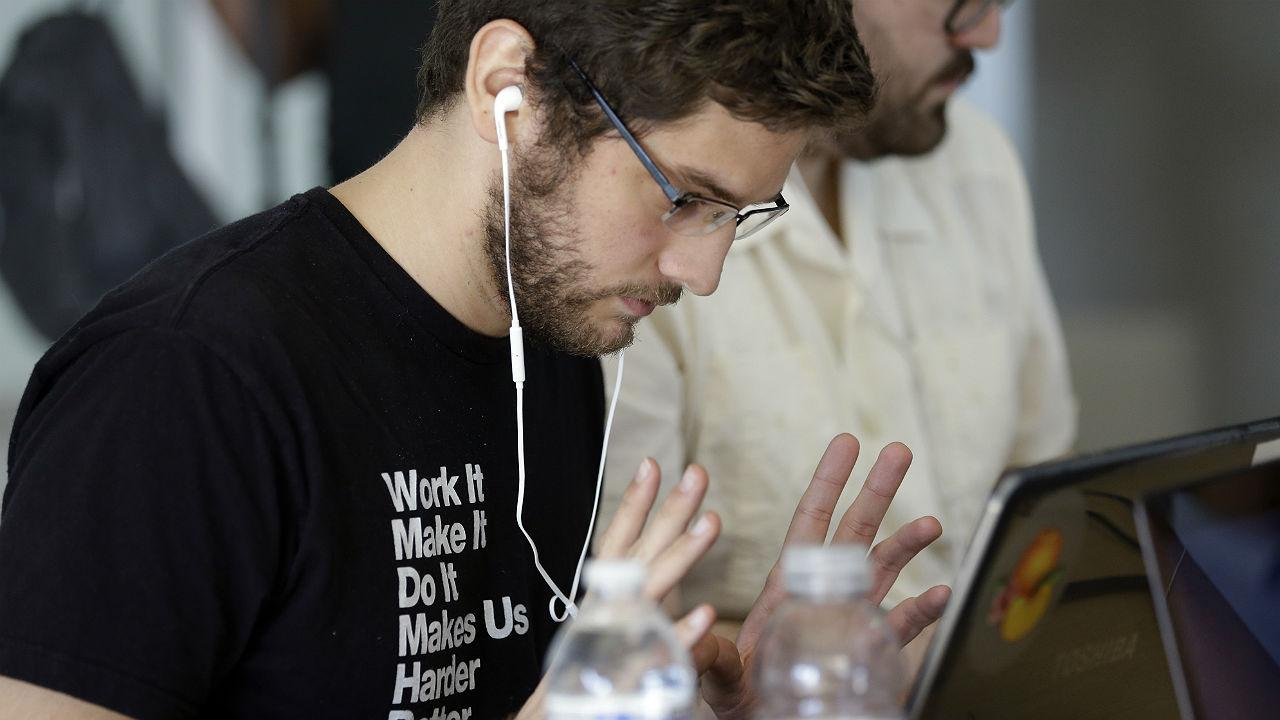 Miguel Chateloin, 23, of Miami works on his computer