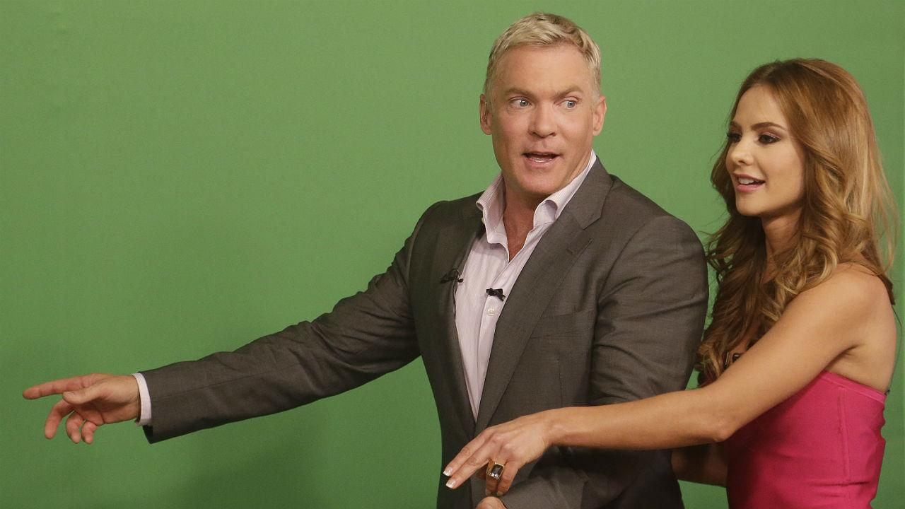 Sam Champion, helps Ximena Cordoba as she does the weather in front of a green screen