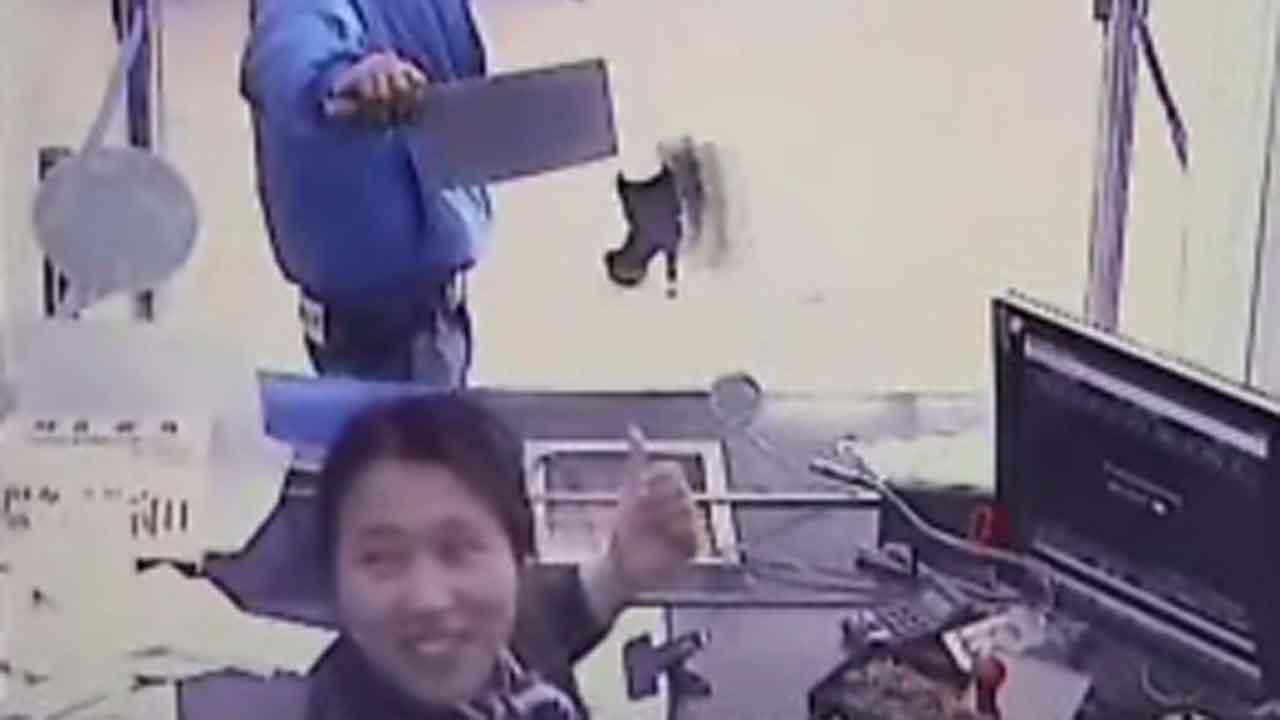 Caught on camera: Bank clerk laughs at cleaver-wielding robber in China