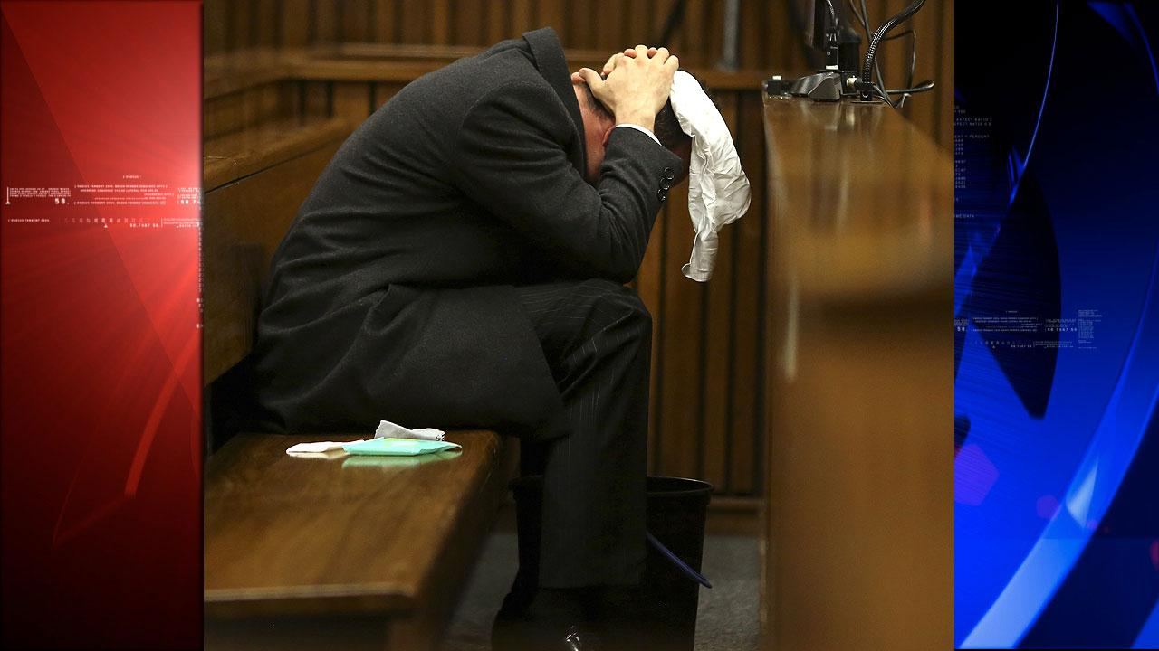 Oscar Pistorius covers his head with a handkerchief
