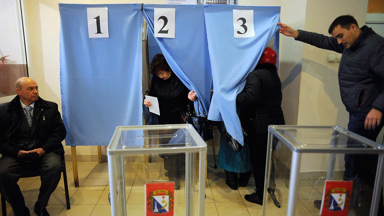 Local residents enter and exit polling booths at a polling station during the Crimean referendum