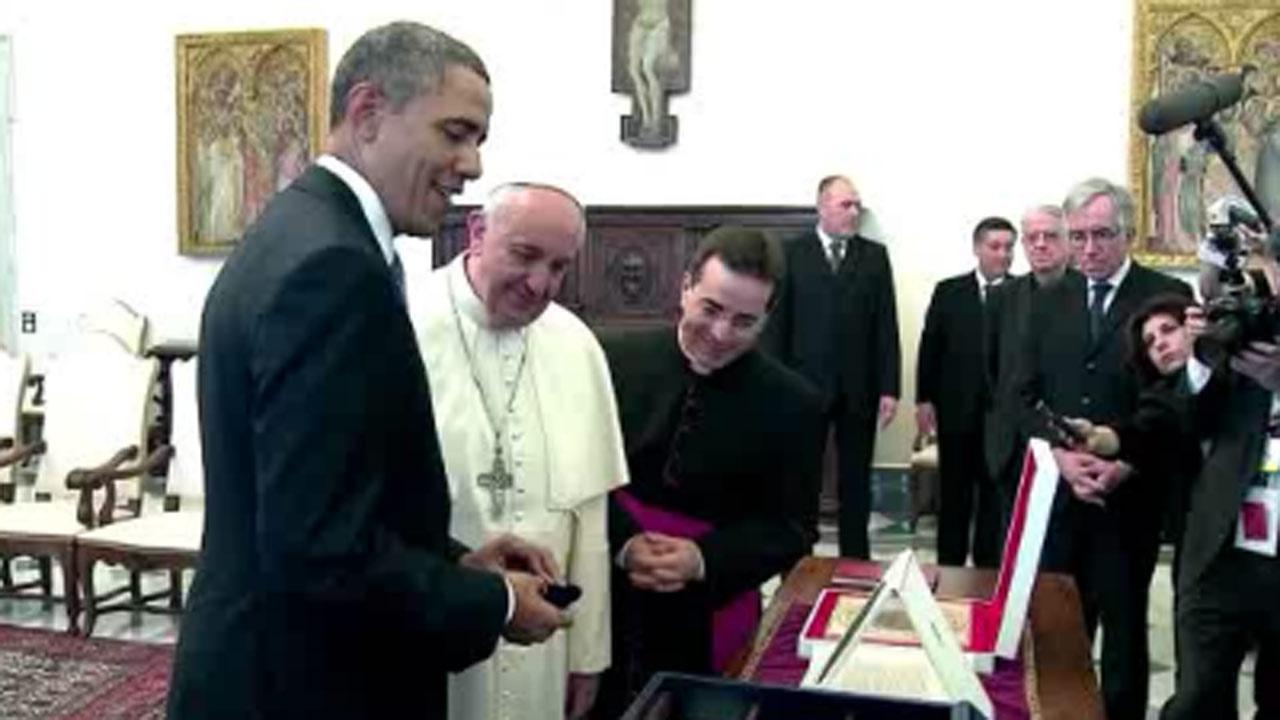 President Obama and Pope Francis look at coins and a large proof on display at the Vatican.