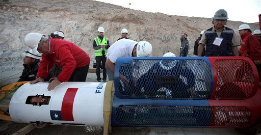 In this photo released by the Chilean government, Chile&#39;s Health Minister Jaime Manalich, left, looks at the rescue capsule that will be used to rescue the 33 trapped miners one by one from the collapsed San Jose mine in Copiapo, Chile, Tuesday Oct. 12, 2010.  The first of 33 trapped miners is expected to be lifted to the surface late Tuesday after surviving more than two months below ground.   &#40;AP Photo&#47;Hugo Infante, Chilean government&#41; <span class=meta>(AP Photo&#47; Hugo Infante)</span>