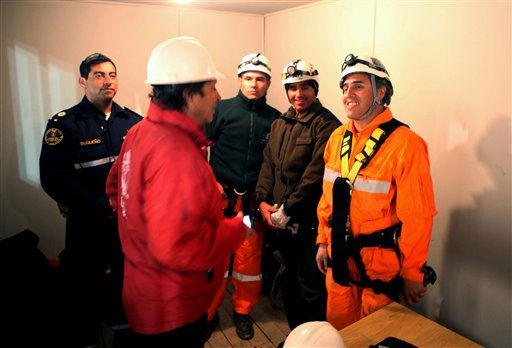 In this photo released by the Chilean government, Manuel Gonzalez, right, a rescue specialist listens to Chile&#39;s Mining Minister Laurence Golborne, second left, before being the first rescuer lowered by a capsule into the hole from which 33 trapped miners will be extracted one by one from the San Jose mine near Copiapo, Chile, Tuesday Oct. 12, 2010.  The first of 33 trapped miners is expected to be lifted to the surface late Tuesday after surviving more than two months below ground.  &#40;AP Photo&#47;Hugo Infante, Chilean government&#41; <span class=meta>(AP Photo&#47; Hugo Infante)</span>