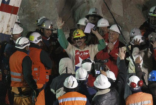 Rescued miner Juan Andres Illanes Palma, center,  third miner to be rescued, salutes at his arrival to the surface from the collapsed San Jose gold and copper mine where he was trapped with 32 other miners for over two months near Copiapo, Chile, Wednesday Oct. 13, 2010.at the San Jose Mine near Copiapo, Chile Wednesday, Oct. 13, 2010. Center right is Chile&#39;s President Sebastian Pinera.&#40;AP Photo&#47;Roberto Candia&#41; <span class=meta>(AP Photo&#47; Roberto Candia)</span>