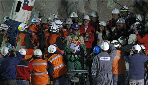 "<div class=""meta image-caption""><div class=""origin-logo origin-image ""><span></span></div><span class=""caption-text"">Rescued miner Carlos Mamani Solis, from Bolivia, center, smiles as he is greeted after being rescued from the collapsed San Jose gold and copper mine where he was trapped with 32 other miners for over two months near Copiapo, Chile, Wednesday Oct. 13, 2010.at the San Jose Mine near Copiapo, Chile Wednesday, Oct. 13, 2010. At right from Mamani is Chile's President Sebastian Pinera holding a Bolivian flag.(AP Photo/Roberto Candia) (AP Photo/ Roberto Candia)</span></div>"
