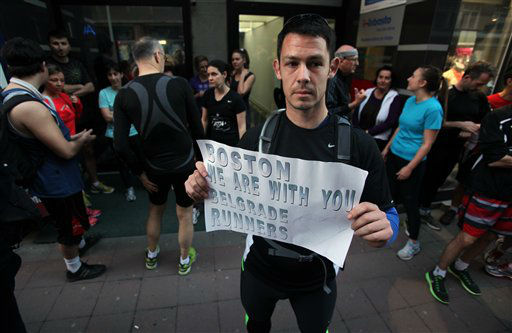 A runner shows a banner reading: &#34;Boston we are with you - Belgrade runners&#34; in an organized memorial run to show solidarity with victims of the Boston Marathon bombing, Tuesday, April 16, 2013, in Belgrade, Serbia. The explosions Monday afternoon killed at least three people and injured more than 140. &#40;AP Photo&#47;Darko Vojinovic&#41; <span class=meta>(AP Photo&#47; Darko Vojinovic)</span>