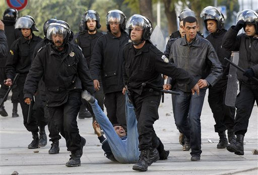 Riot police officers detain a protestor during clashes in Tunis, Friday, Jan. 14, 2011.  Tunisia&#39;s president declared a state of emergency and announced that he would fire his government as violent protests escalated Friday, with gunfire echoing in the North African country&#39;s usually calm capital and police lobbing tear gas at protesters.  <span class=meta>(AP Photo&#47; Christophe Ena)</span>