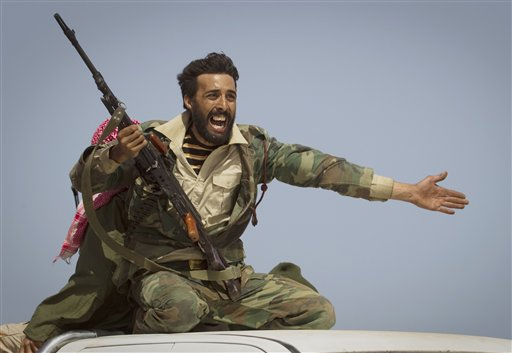 A Libyan rebel urges people to leave, as shelling from Gadhafi&#39;s forces started landing on the frontline outside of Bin Jawaad, 150 km east of Sirte, central Libya, Tuesday, March 29, 2011.     <span class=meta>(AP Photo&#47; Anja Niedringhaus)</span>