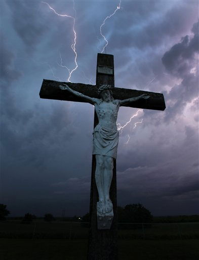 Lightning from a severe thunderstorm flashes in the distance beyond a crucifix in a cemetery near Easton, Kan. Saturday, May 21, 2011.  <span class=meta>(AP Photo&#47; Charlie Riedel)</span>