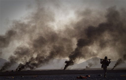 A US Marine on his way to pick up food supplies after they were dropped off by small parachutes from a plane outside Forward Operating Base Edi in the Helmand Province of southern Afghanistan, Thursday, June 9, 2011. The smoke in the background comes from burning parachutes the Marines destroy after they reached the ground.    <span class=meta>(AP Photo&#47; Anja Niedringhaus)</span>