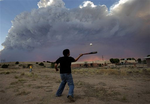 Alex Lopez, center, plays baseball with his sister Sugey while smoke generated by the Las Conchas fire covers the sky in Espanola, N.M., Wednesday, June 29, 2011. As crews fight to keep the wildfire from reaching the country&#39;s premier nuclear-weapons laboratory and the surrounding community, scientists are busy sampling the air for chemicals and radiological materials.   <span class=meta>(AP Photo&#47; Jae C. Hong)</span>