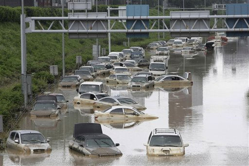 Vehicles are submerged in floodwater after heavy rain in Seoul, South Korea, Thursday, July 28, 2011. Thousands of rescuers used heavy machinery and shovels Thursday to clear mud and search for survivors after huge landslides and flooding killed more than 40 people in South Korea.  <span class=meta>(AP Photo&#47; Ahn Young-joon)</span>
