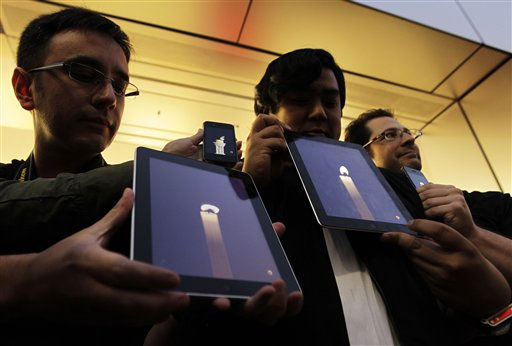 Apple computer fans hold their iPhones and iPads displaying candle graphics during a candle light vigil to pay tribute to Steve Jobs, the Apple founder and former CEO, at an Apple Store in the Ginza shopping district in Tokyo Thursday, Oct. 6, 2011. Apple announced Jobs&#39; death without giving a specific cause. He died on Wednesday at the age of 56.   <span class=meta>(AP Photo&#47; Hiro Komae)</span>