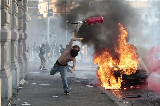 "<div class=""meta image-caption""><div class=""origin-logo origin-image ""><span></span></div><span class=""caption-text"">A protestor hurls a canister towards police next to a burning car during clashes in Rome, Saturday, Oct. 15, 2011. Protesters in Rome smashed shop windows and torched cars as violence broke out during a demonstration in the Italian capital, part of worldwide protests against corporate greed and austerity measures, entitled Occupy Wall Street.  (AP Photo/ Gregorio Borgia)</span></div>"