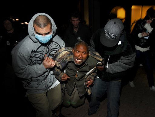 Protesters help an injured Occupy Oakland demonstrator after a police-fired projectile struck his leg on Thursday, Nov. 3, 2011, in Oakland, Calif. Following a mainly peaceful day-long protest by thousands of anti-Wall Street demonstrators, several hundred rallied through the night with some painting graffiti, breaking windows and setting file to garbage cans.