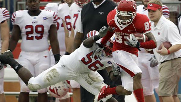 Houston wide receiver Patrick Edwards &#40;83&#41; is pushed out of bounds by SMU linebacker Ja&#39;Gared Davis &#40;56&#41; after catching a pass good for a first down during the first quarter of an NCAA college football game on Saturday, Nov. 19, 2011, in Houston. &#40;AP Photo&#47;David J. Phillip&#41; <span class=meta>(AP Photo&#47; David J. Phillip)</span>