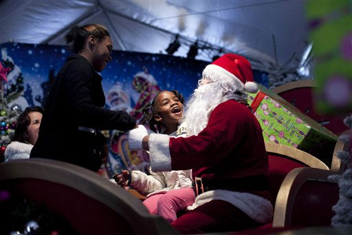 Alisandre Young, center, tells Santa Claus her Christmas wishes at the Los Angeles Mission Christmas event in the Skid Row area of downtown Los Angeles, Friday, Dec. 23, 2011. &#40;AP Photo&#47;Jae C. Hong&#41; <span class=meta>(AP Photo&#47; Jae C. Hong)</span>